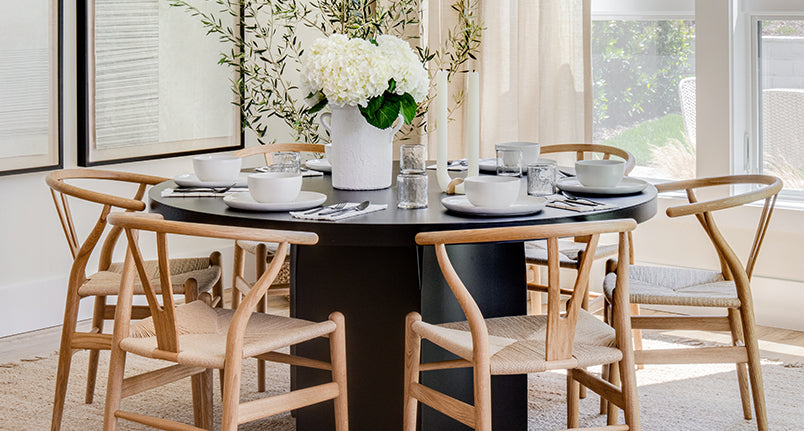 Coastal Scandinavian dining room setting with wood wishbone chairs and black metal round table