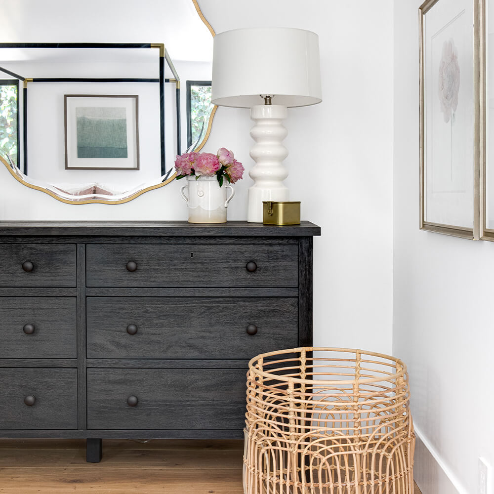 Flowery girls bedroom with dark wood dresser, white Palisades lamp and Adagio cane basket