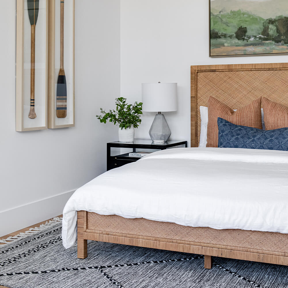 Photo of a bedroom with canoe oars as artwork and black and white woven rug