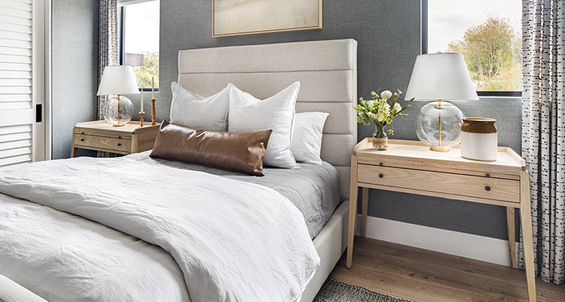 Tufted bed with gray duvet and pillows, with two wood nightstands