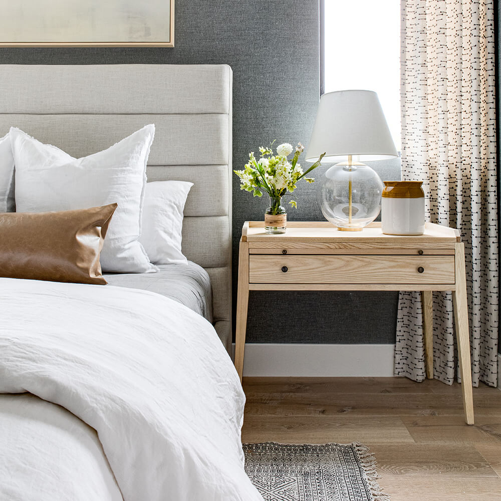Coastal bedroom interior design with tufted gray bed and modern light wood nightstand