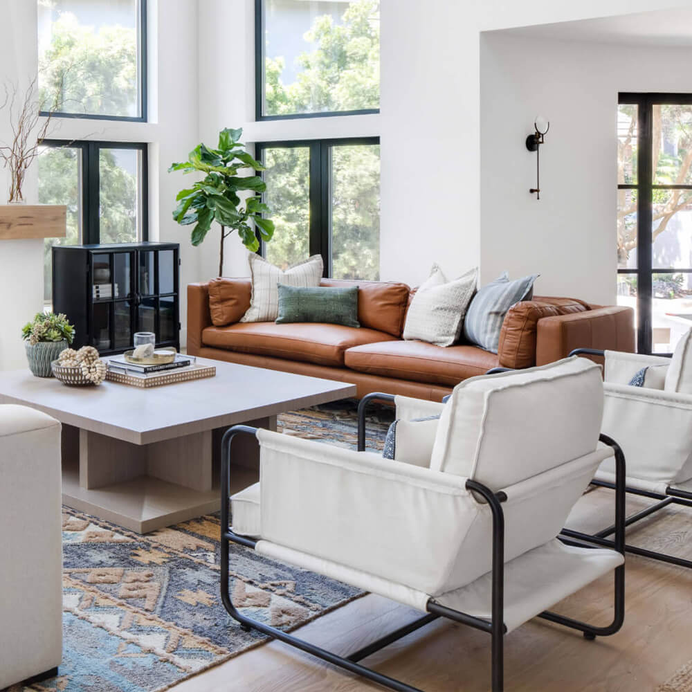 Photo of a Spanish modern living room with a leather sofa and two canvas accent chairs around a square coffee table