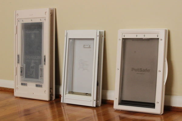 reviewing the dragon, petsafe, and ideal pet doors all lined up against the wall