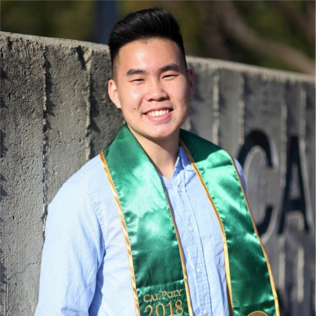 a man in a blue shirt with a green university sash on his shoulders smiling at the camera