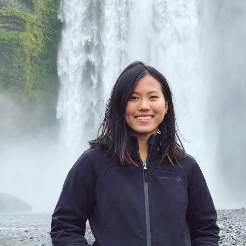 a dark haired woman in a black jacket smiling in front of a waterfall