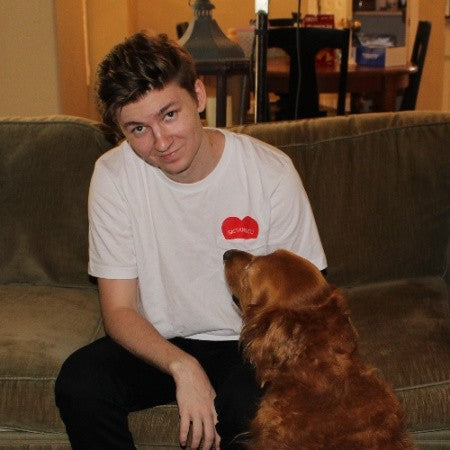 a man in a plain white shirt sitting on a couch, petting a golden retriever
