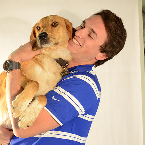 A smiling man in a blue striped shirt holding a golden retriever in his arms