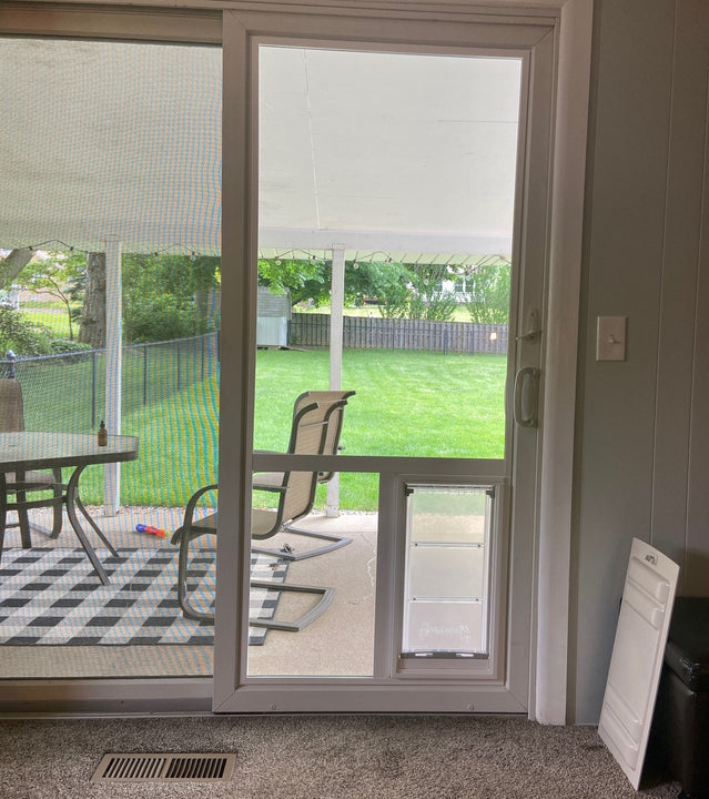 A sliding glass door with an Endura Flap pet door installed directly into the glass.