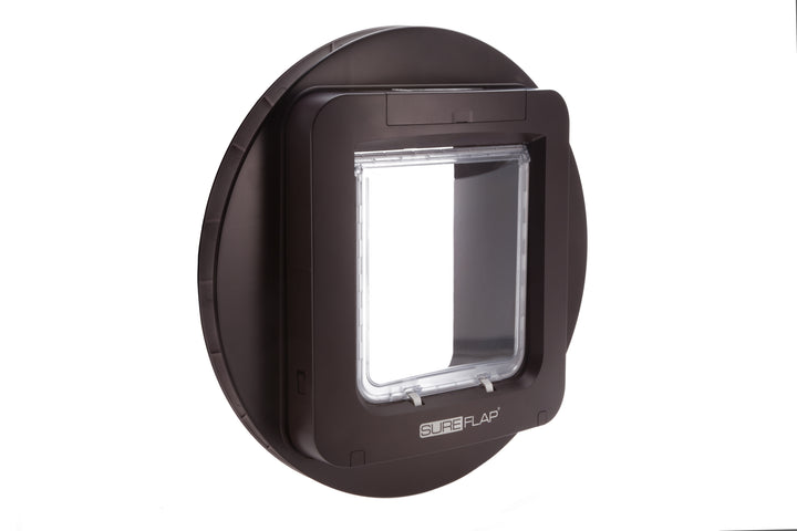 The Sureflap Microchip Cat Door Mounting Adapter with a brown frame can mount the door through metal, glass, walls, and thin materials
