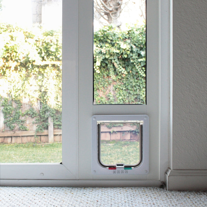 The green and red tabs on the Whiskers and Windows cat flap control the settings of the four-way locking system