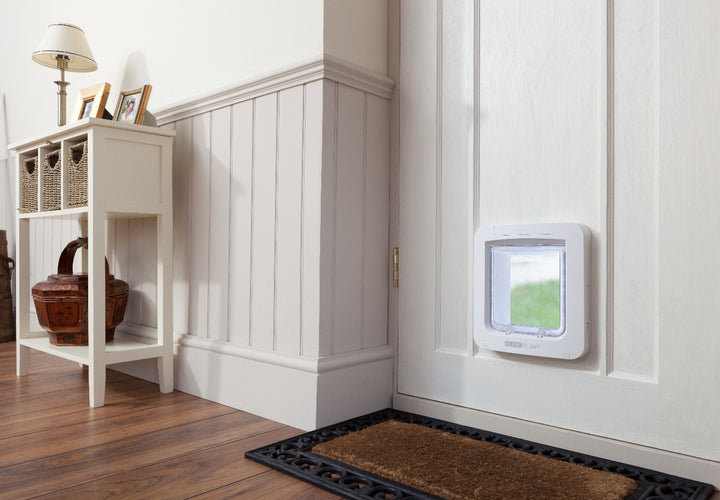 Image of white framed Sure Petcare Sureflap Microchip Pet Doors for Doors installed in a white front door of a home