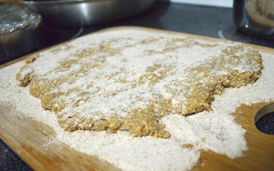 Rolled out dough on surface prepared with flour for homemade dog biscuits