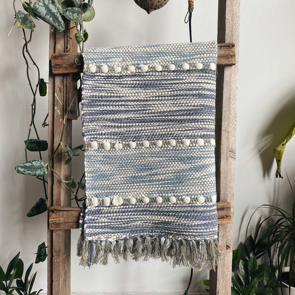 Striped handwoven blue and white cotton rug hanging on a wooden ladder