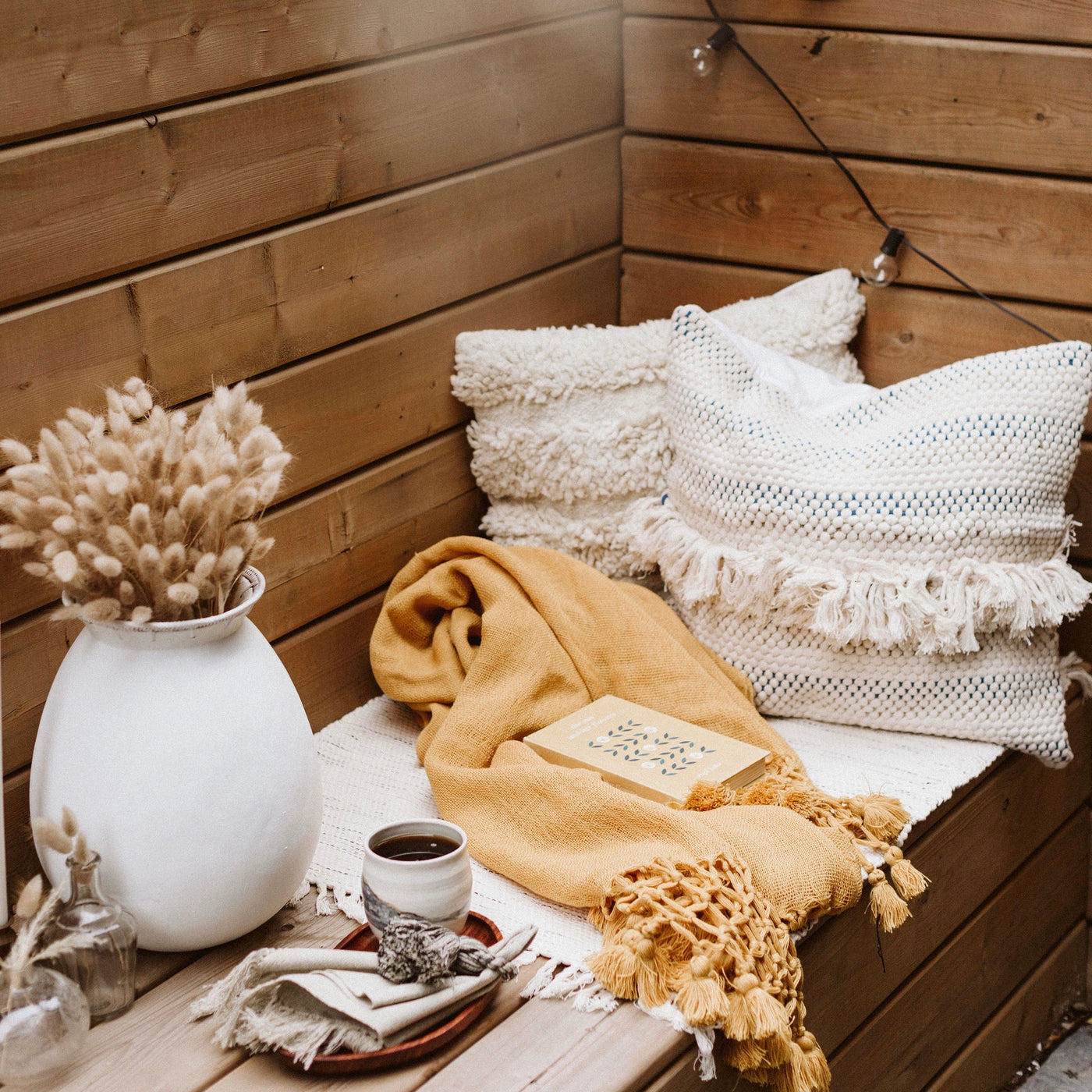 Wooden bench with textured pillows, blankets, and vase