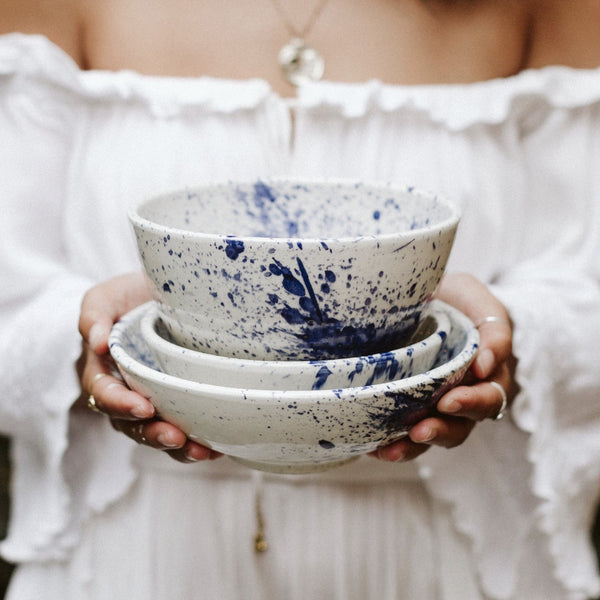 Woman holding hand-painted white and blue bowls