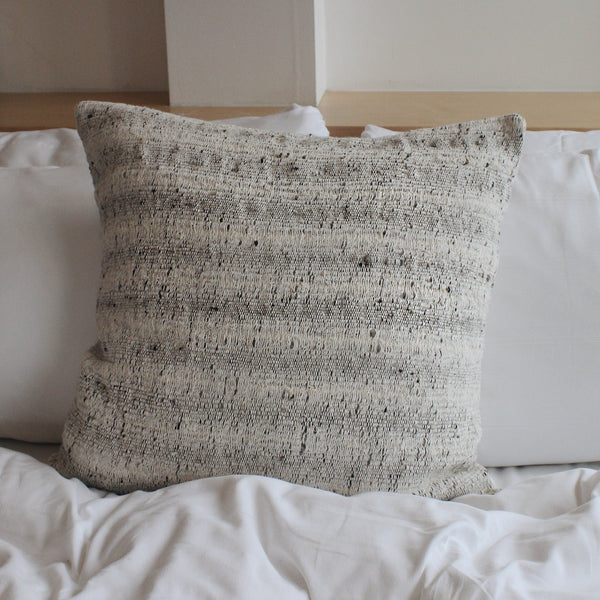 Textured cotton accent pillow on a bed
