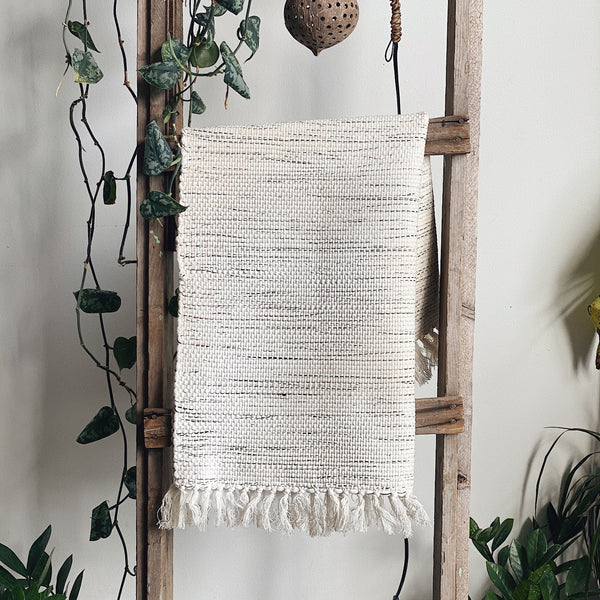 Textured black and white rug hanging on a wooden ladder