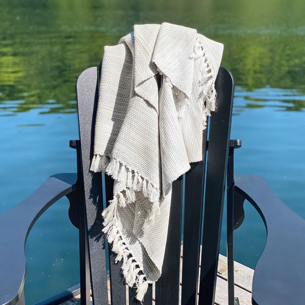 Soft textured blanket on a chair in front of a lake