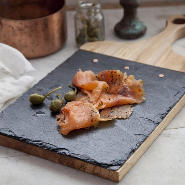 Slate and wood paddle serving board with appetizers
