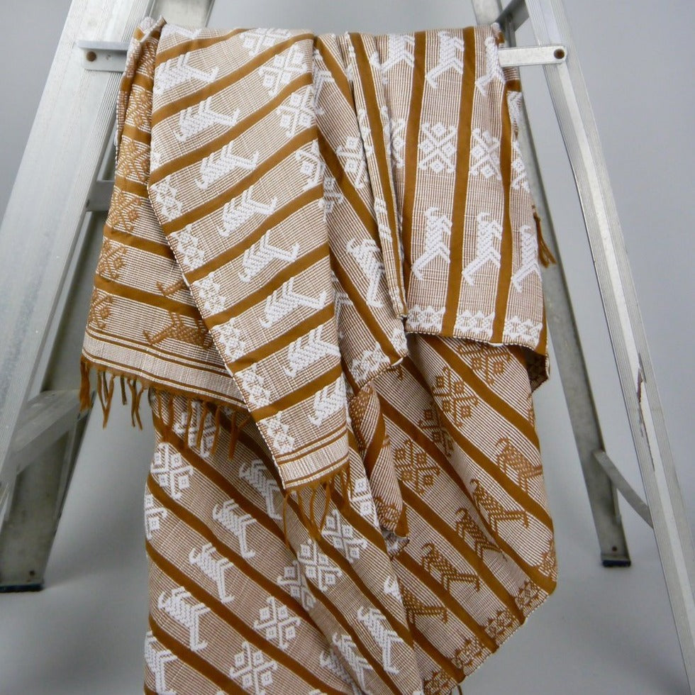 Handwoven patterned throw on a ladder