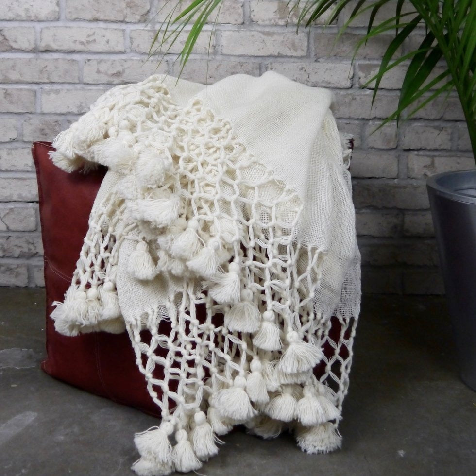 Ivory wool blanket on a leather stool