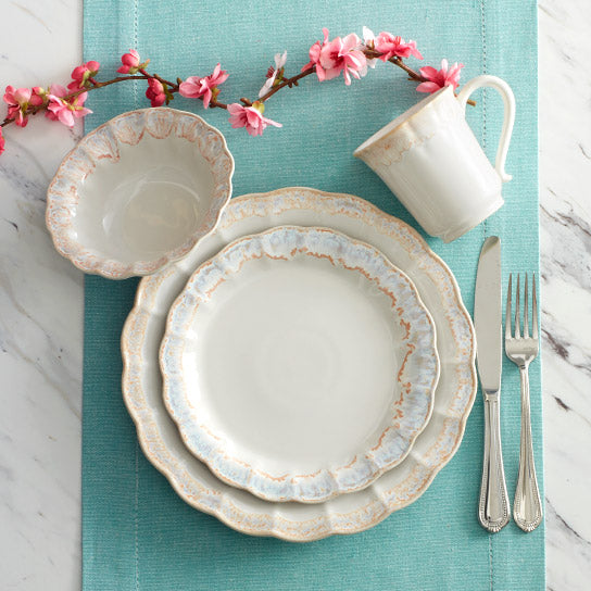 The shapes and scalloped edges of Mila dinnerware bring to mind tradition and elegance, yet the rims have a subtle wash of blue and tan that add a contemporary, abstract accent.