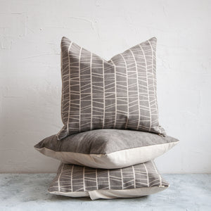 Stack of botanically dyed, organic cotton cushions with geometric screen print