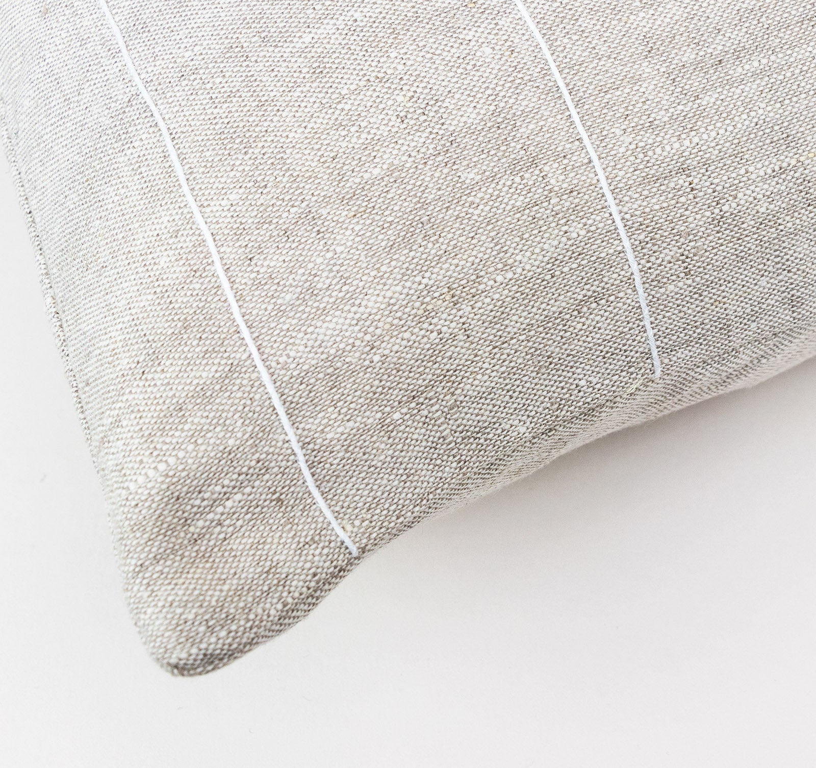 Embroidered detailing of white stripe on beige linen cushion cover