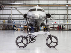 Bespoke white ebike in front of plane