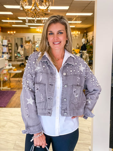 Pearl embellished and embroidered denim jacket in grey/lavender with white button down and black slacks.