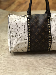 White hair on hide bag with gold acid wash accents and repurposed authentic Louis Vuitton stripe down either side with gold studs and leather handles at Fruit of the Vine Online Boutique from Jaded Gypsy/Gypsy Junkies.