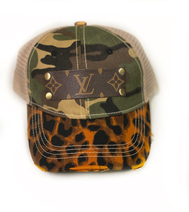 Repurposed Louis Vuitton trucker, snap back hat with leopard print distressed bill and camo accent. Classic monogram Louis Vuitton emblem