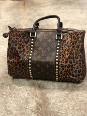 Dark leopard or cheetah print hair on hide repurposed Louis Vuitton speedy bag from Gypsy Junkies/Jaded Gypsy. Gold studded details along either side of LV strips on both sides of the bag, double zipper closures and leather straps.