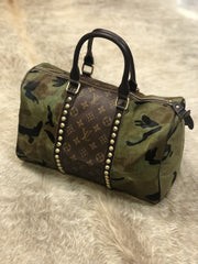 Repurposed Louis Vuitton Speedy Bag in Camo print. Authentic repurposed Louis Vuitton strips down the middle along either side of the bag. Double zipper closure, gold studded details and leather straps.