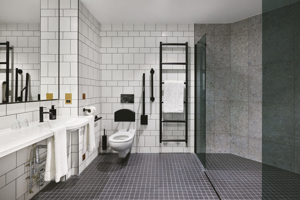 A white tiled wet room  with black brassware and grey floor