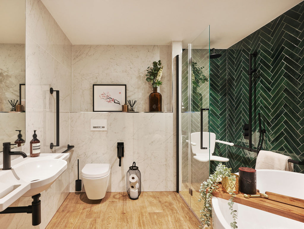 Sophie's new bathroom. Toilet area is white marble tiled, shower area is deep mottled green subway tiles laid in a herringbone pattern. Wood-effect floor tiles throughout and matt black grab rails. Artwork, flowers and candles sit on a built-in shelf behind the toilet. The edge of a large curved bath in the foreground has a wooden bath board across it, decorated with plants and bath salts. A white shower seat is in the shower area behind a single folding glass screen.