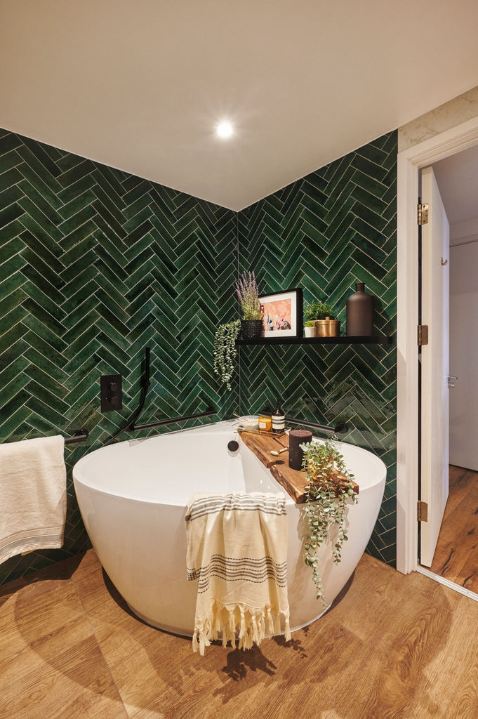 Corner view of Sophie's new bathroom, focused on curved floor standing corner bath. Surrounded by rich mottled green subway style tiles in a herringbone pattern. Wood-effect floor tiles on the floor and a black shelf full of plants and artwork just above the bath. A wooden bath board sits across the bath, decorated with plants, towels and bath salts.  Matt black grab rails subtly blend into the green tile around the bath.