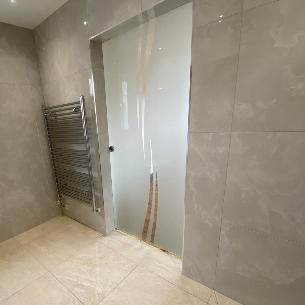 N's new level access ensuite, with neutral tiles and frosted glass door