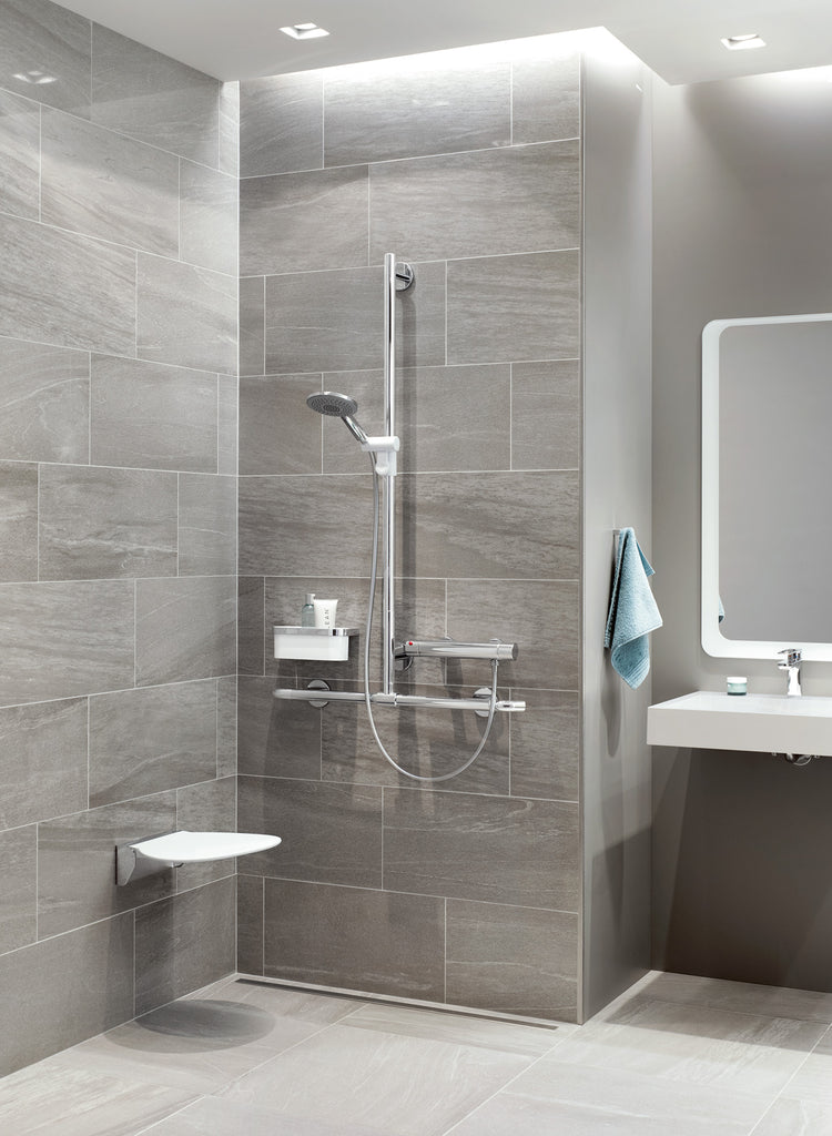 A shower area with a white fold up shower seat and chrome T-shaped grab rail riser rail to the left