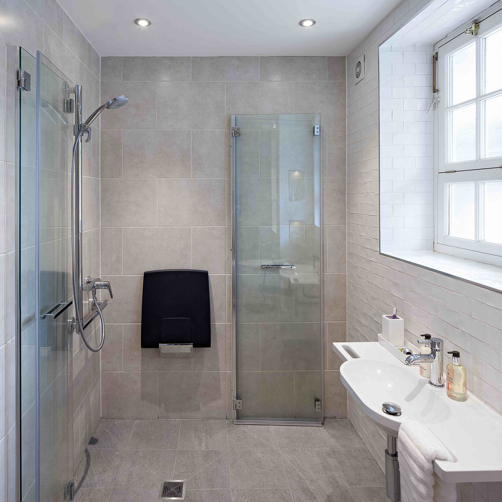Kate's fully newly future-proofed bathroom with space fully opened up, shower seat and bi-fold doors folded against the wall.