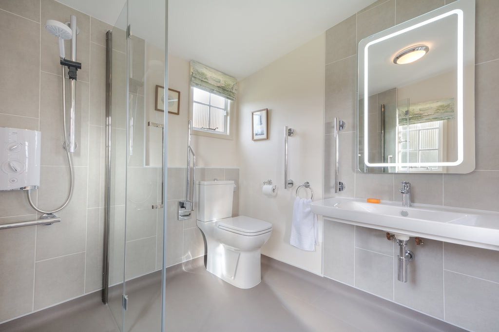 National Trust accessible holiday cottage bathroom after transformation, focussing on comfort height toilet.