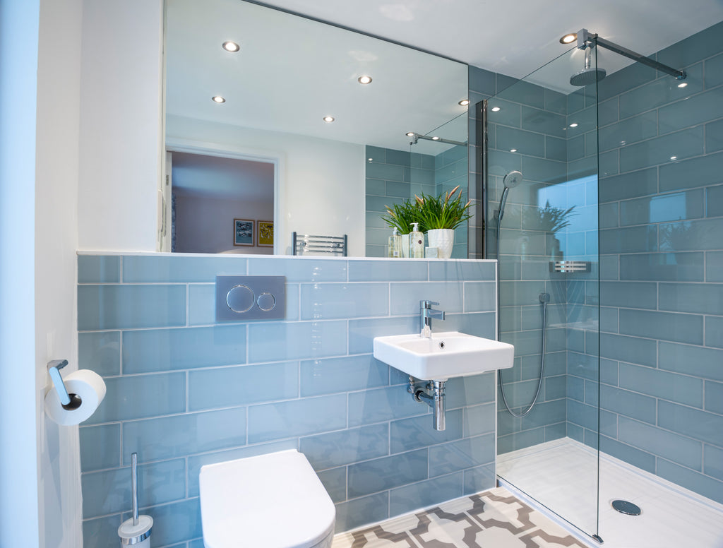 blue tiled shower room with a large mirror behind the toilet and basin. A chrome corner storage caddy is in the shower area.