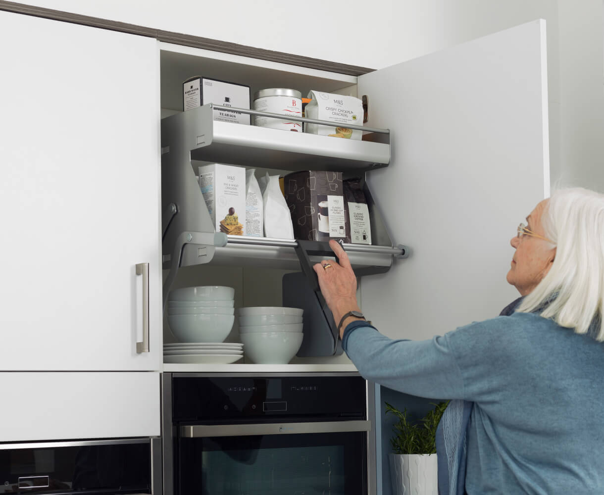 Older lady pulling down drop-down kitchen cupboard baskets from a cabinet above her