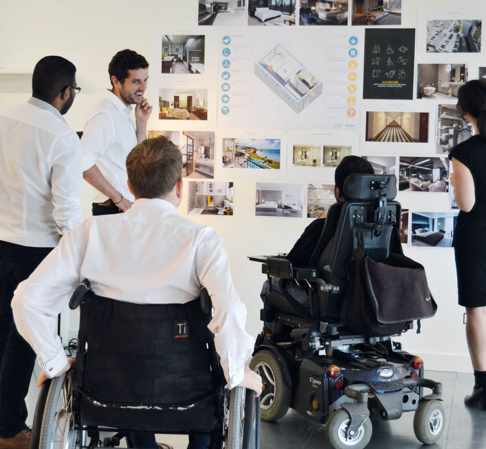 Five people, some standing, some seated in wheelchairs, discussing designs on a wall together.