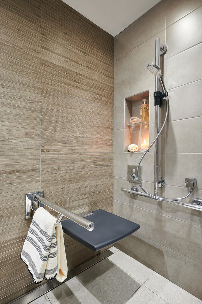 A wet room shower area featuring a recessed storage niche beside the shower riser rail