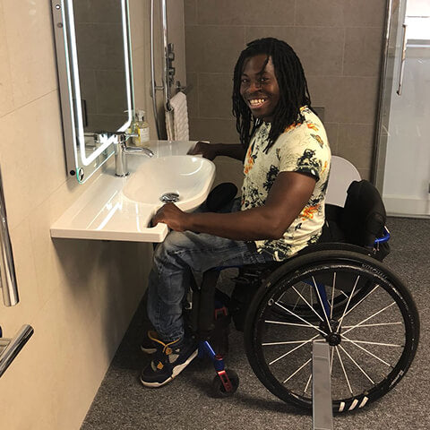 Paralympian Ade Adepitan testing a Fine & Able wash basin with hand grips in show room.