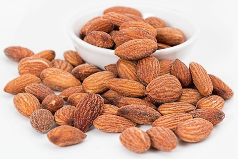 Almonds placed in and around a small, white bowl