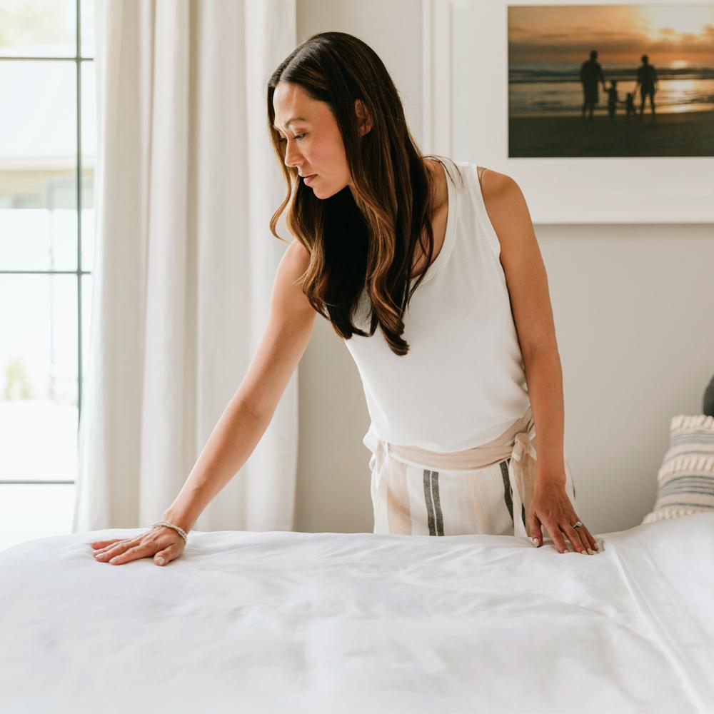 Woman smoothing the synthetic duvet insert
