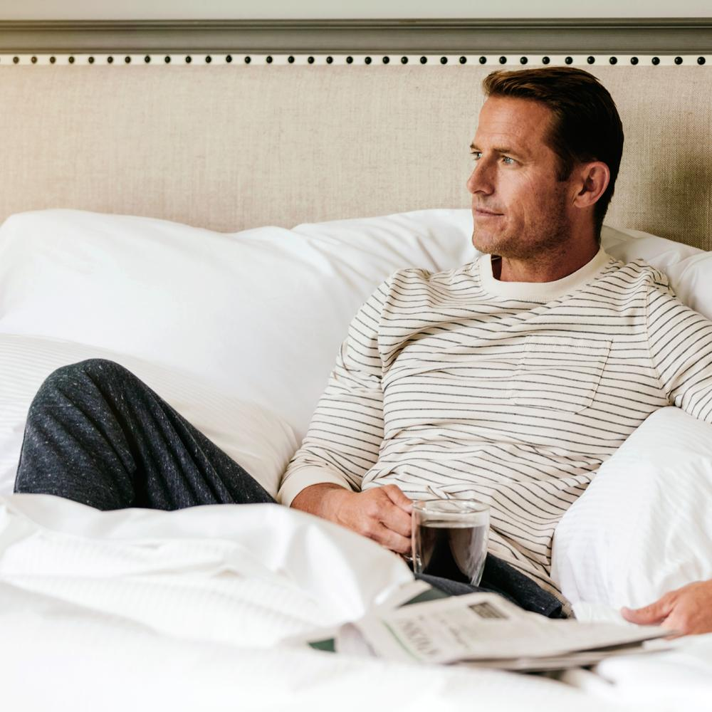 Man drinking coffee on The Fairmont Bed