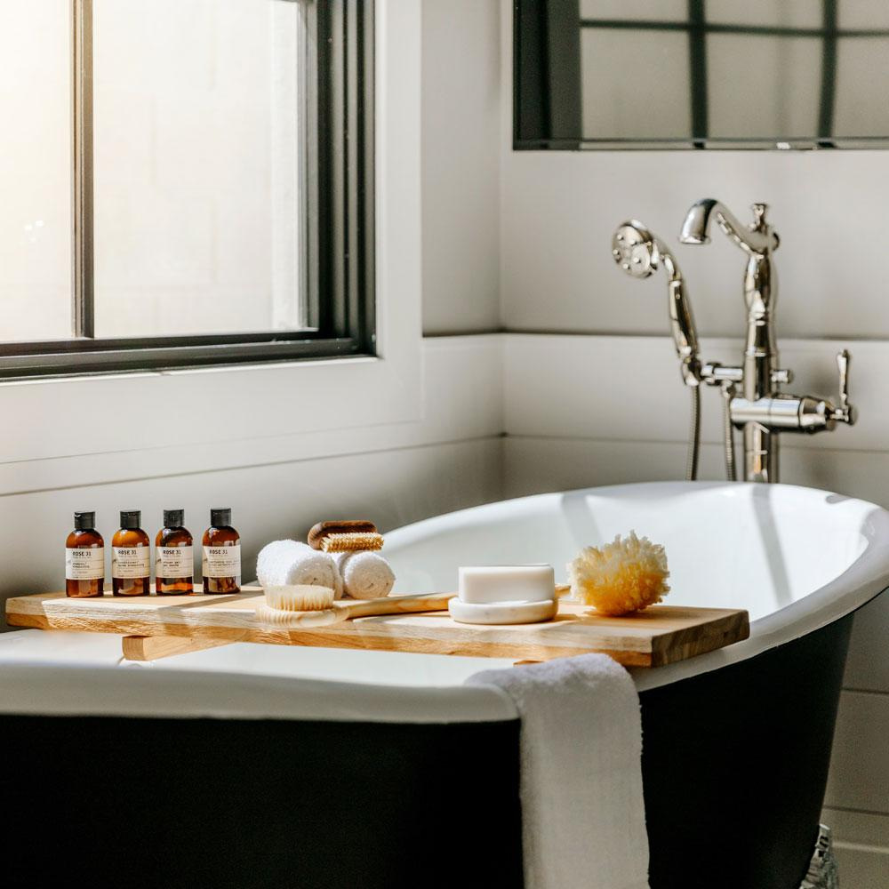 Le Labo Rose 31 travel size bottles and other products on bath tub
